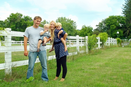 a happy, attractive family of four people, a mother, father, baby and young child are standing outside by a white picket fence on a summer day photo