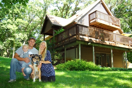 A young, attractive, happy family of three; mother, father, and baby, sit with their dog outside a large cabin in the woods