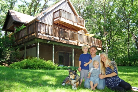 een jonge, aantrekkelijke, gelukkig gezin van vier, moeder, vader, baby, en jong kind, zit buiten met hun hond voor een beautful cabine op een zonnige zomerdag