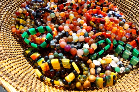 A close up of strands of rainbow colored bead jewelry in a woven basket photo