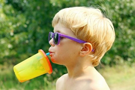 a young boy wearing purple sunglasses is tipping his head back drinking juice from a colorful sippy cup on a sunny summer day photo