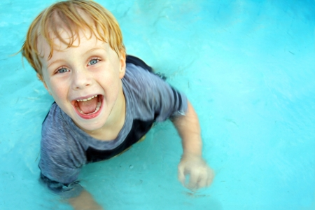 a cute, happy child is smiling as he looks up at the camera and jumps around in a swimming pool on a hot summer day.  Empty Room on Water for text  copy space. photo