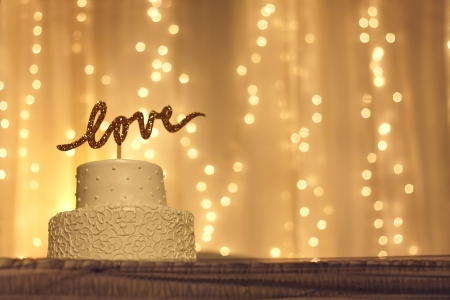 reception room: a simple white wedding cake with the word love written in sparkling gold letters on the top, with white twinkling lights and fabric in the background Stock Photo
