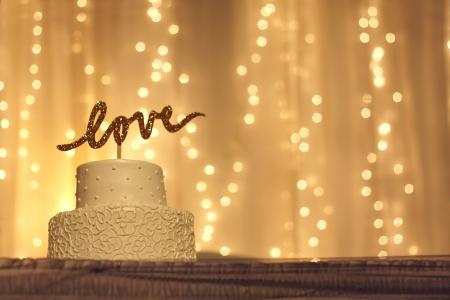 een eenvoudige witte bruidstaart met het woord liefde geschreven in fonkelende gouden letters op de top, met witte twinkelende lichtjes en stof op de achtergrond