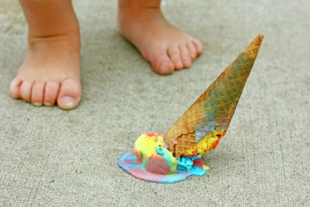 foot cream: a dropped rainbow colored ice cream cone lays upside down on the sidewalk at the feet of a young child