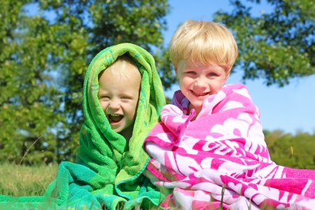 Two happy young children; a little boy and his baby brother are smiling as the sit wrapped together in vibrant colorful beach towels on a sunny summer day photo