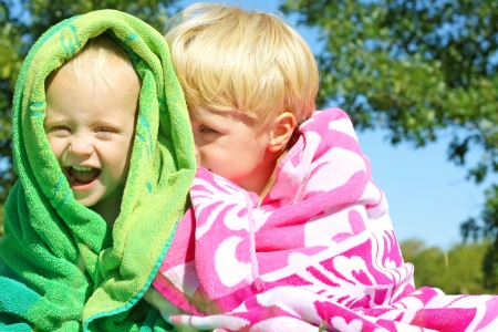 Two happy young children; a little boy and his baby brother, are laughing and snuggling under bright colorful beach towels outside on a sunny day photo