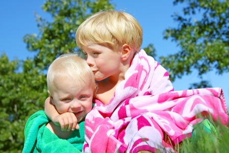 a young child is kissing is baby brother on the cheek as they sit outside in colorful beach towels on a sunny summer day photo