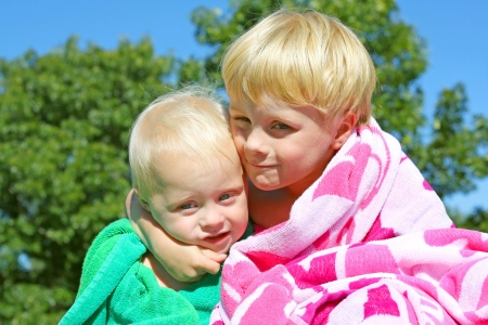 a young child is hugging his baby brother as they sit outside in the grass in beach towels on a sunny summer day photo