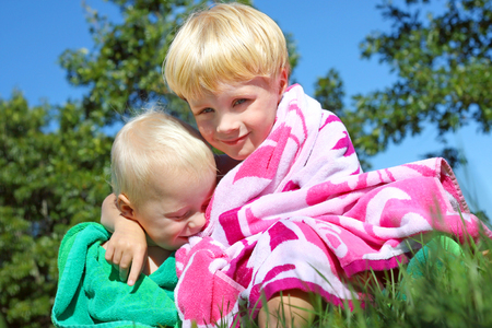 Two happy brothers, a baby and a young child, outside hugging each other in colorful beach towels on a sunny summer day  photo