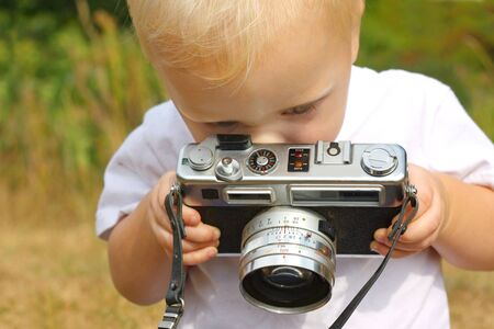 a cute baby boy is sitting outside on a fall day, playing with a vintage camera photo