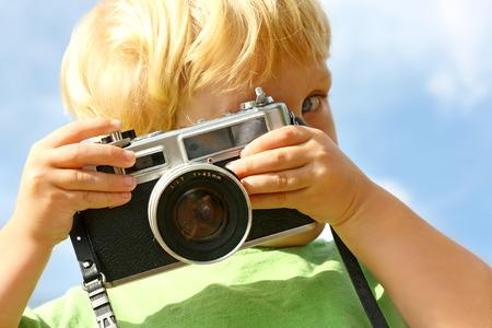 若い男の子が外で遊ぶ間、ビューアーで、ビンテージ カメラを指しています。 写真素材