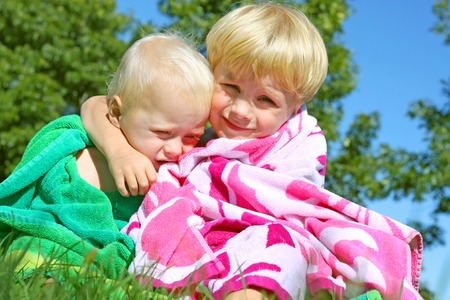 Two brothers, a baby and a youg child, hugging each other outside in a beach towel on a sunny summer day  photo