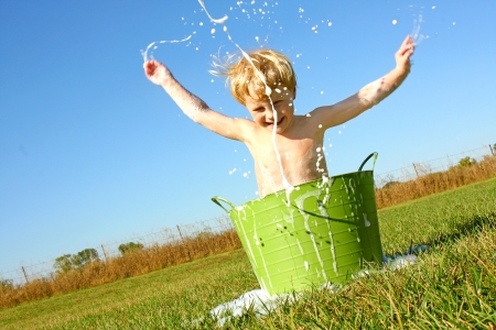 a happy young boy is playing outside in a small green wash basin, and is splashing bubble water in the air on a summer day Stock Photo
