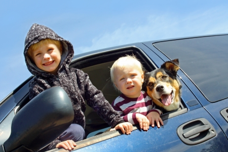 Two happy young children and their cute German Shepherd dog are leaning out the side window of a blue minivan photo
