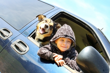 a small child wearing a black hooded sweatshirt and his German Shepherd dog are sticking their heads out a van window