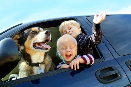 Two happy little children and their German Shepherd Dog are waving and peeking their heads out the window of a van