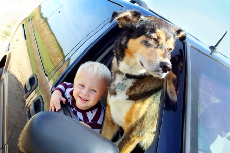 a cute, smiling baby boy and his German Shepherd dog are hanging out a minivan window on a summer day photo