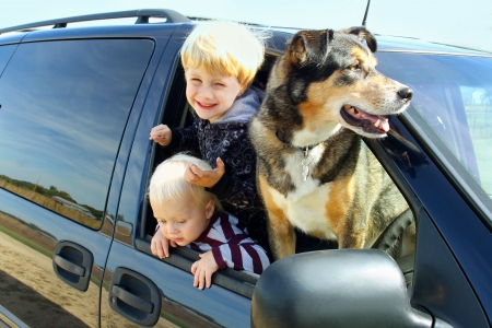 wo happy young children and their German Shepherd dog are hanging out the window of a minivan