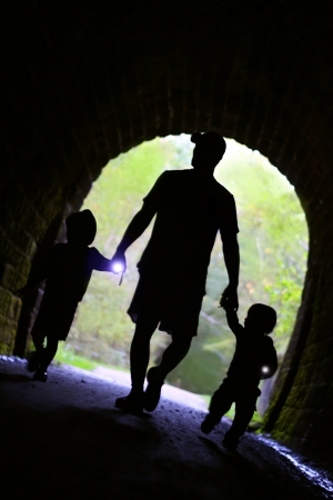 a father and his two children, a little boy and a baby are holding hands, and flashlights and walking down a trail into a dark stone tunnel photo