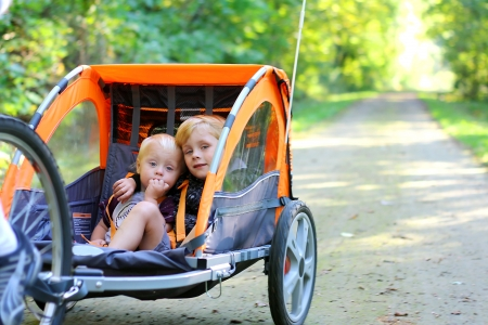 Two young children are sitting together in a pull behind bicycle trailer as they ride down a bike trail in the woods