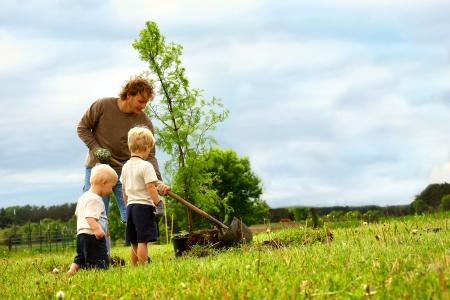 젊은 아버지와 그의 두 아이는 밖에서 마당에 새벽 레드 우드 나무를 심는