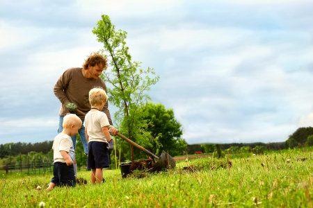 a young father and his two children are outside planting a Dawn Redwood Tree in their yard Stock Photo