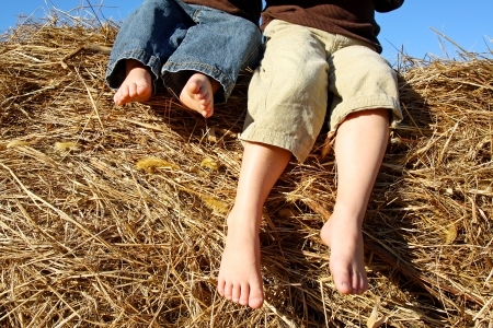 dirty feet: The feet of two small children can be seen hanging off the top of a hay bale outside on an autumn day Stock Photo