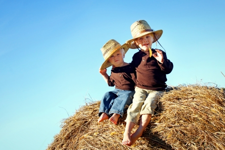 Two children, a young boy and his baby brother are sitting outside on hay bales, wearing straw hats on a sunny Autumn day  Room for Text, Copy Space