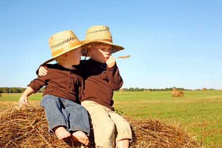 Two young children, a boy and his baby brother, are sitting on a hay bale in a field on a farm, wearing straw cowboy hats   photo