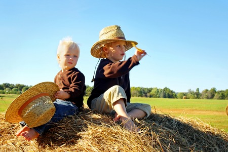 bale: Two happy little boys, a 4 year old and his baby brother, are sitting outside on top of a large hay bale, wearing straw hats on a sunny autumn day