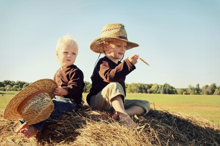 Two young kids, a little boy and his baby brother, are sitting on top of a hay bale wearing straw hats on a sunny autumn day   Vintage Style Coloring