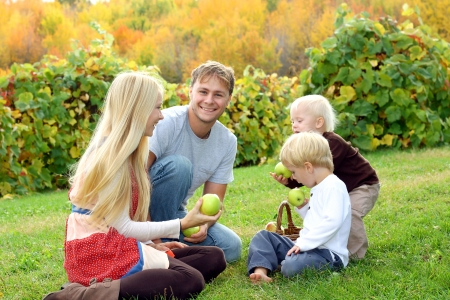 a young, attractive, happy family of four people, mother, father, baby, and young child, are sitting outside at an apple orchard, in front of colorful autumn trees photo