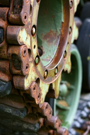 tred: close up on the wheels, a caterpillar track, of an old Military Tank, which resemble gears