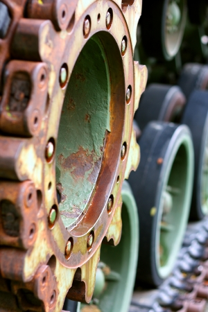 tred: an extreme close up of the wheels of an old, camouflage military tank, which appear as circular gears.  Shallow Depth of Field.