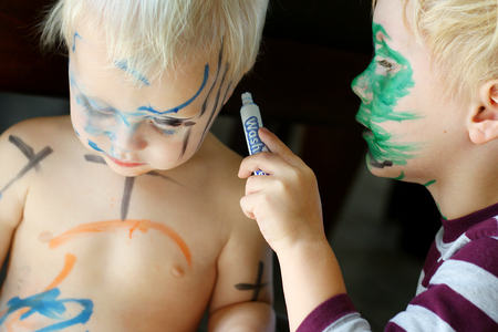 messy: A young child his carefully coloring with a marker all over his baby brothers face and skin Stock Photo