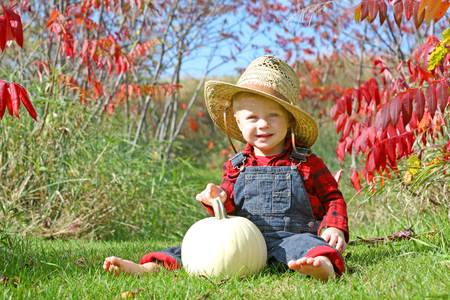 flannel: a cute, smiling baby boy is sitting outside in the grass with a white pumpkin on a sunny autumn day, wearing a straw hat, flannel, and overalls like a little farmer Stock Photo