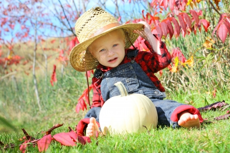 flannel: a cute baby boy is sitting outside in the grass with a white pumpkin on a sunny autumn day, wearing a straw hat, flannel, and overalls like a little farmer