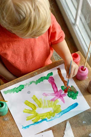 a creative young child can be seen from above painting a happy picture of sun, grass and trees on a piece of paper Reklamní fotografie