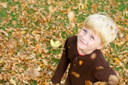 a cute, smiling young boy is looking up in the air as leaves fall around him while playing outside on an autumn day photo