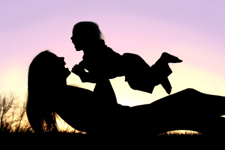 bouncing: a silhouette of a happy, laughing mom is laying in the grass at sunset, lifting her baby boy up into the air over her head Stock Photo