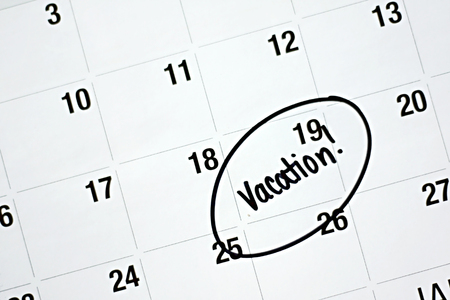 circled: the word vacation is written in black marker and circled on a white monthly calendar Stock Photo