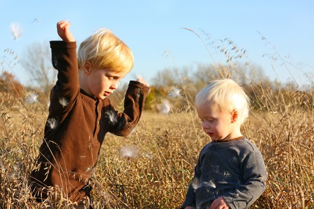 Two young children, a little boy and his baby brother, are playing outside in the country throwing fuzzy milkweed seeds in the air photo