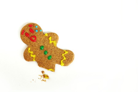 gingerbread cookie: a Christmas Gingerbread Cookie man is upset because someone has eaten his leg, and crumbs are left behind on an isolated white background Stock Photo