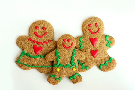 A  Christmas Gingerbread cookie family of man, woman, and child is isolated on a white background photo