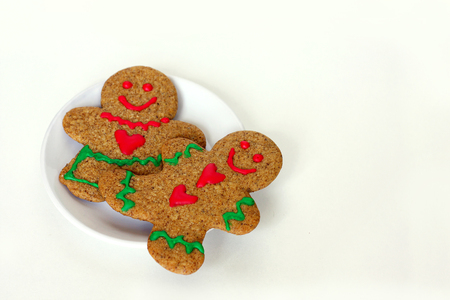 A Christmas gingerbread man cookie with hearts on his shirt is laying on a white plate with a gingerbread woman, on a white isolated background, with room for copy space photo