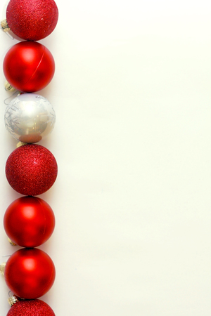 a row of red and silver sparkly christmas ornaments are lined up vertically on a white background Stock Photo