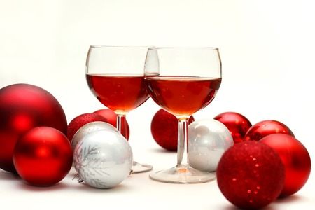 Two wine glasses filled with red wine sit on an isolated white background in surrounded by silver and red sparkling Christmas Bulb Decorations photo