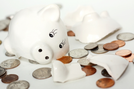 empty handed: a small white piggy bank has just been broken into pieces and coin money is lying scattered around it, isolated on a white background