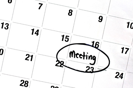 desk calendar: the word meeting has been written on a day of a monthly calendar, in bold, black, permanent marker. Stock Photo